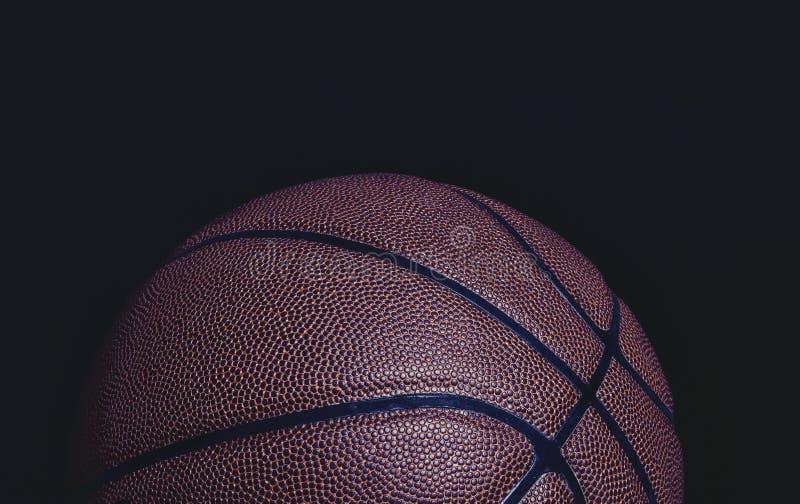 Grungy Nahaufnahme der H?lfte Basketballs auf einem schwarzen Hintergrund lizenzfreies stockbild