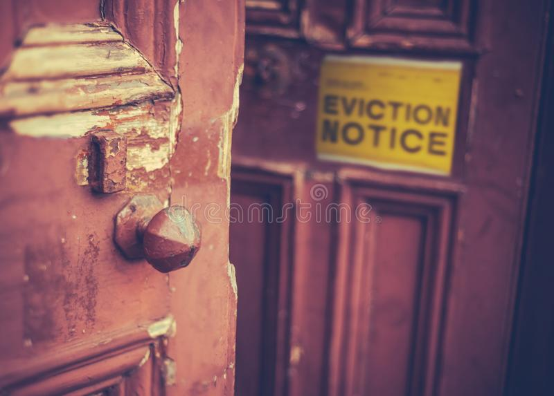 Eviction Notice On Door. Grungy Old Door With A Yellow Eviction Notice royalty free stock photo