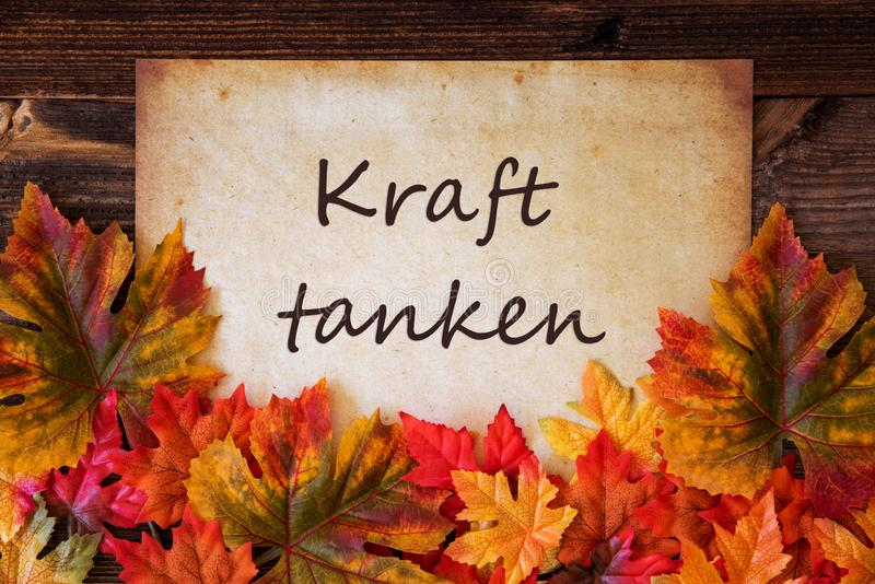 Grungy Old Paper, Colorful Leaves, Kraft Tanken Means Relax. Grungy Old Paper With German Text Kraft Tanken Means Relax. Colorful Autum Decoration With Leaves stock images