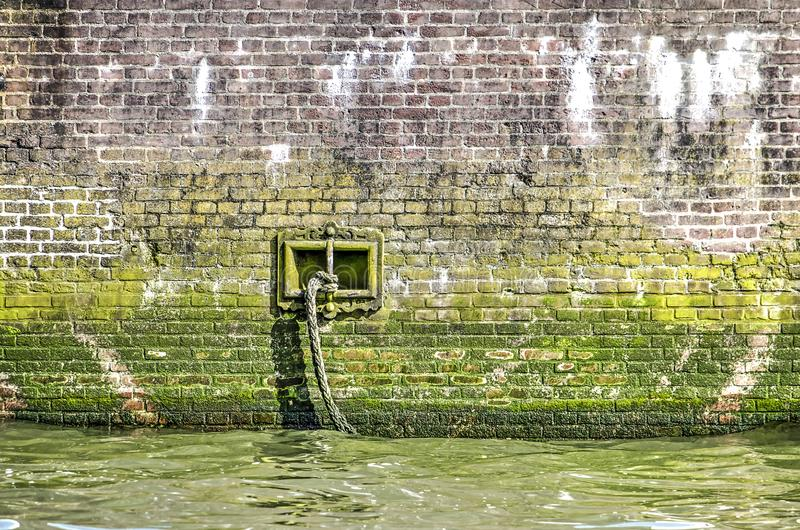 Grungy quaywside wall with rope. Old, dirty, grungy and mossy brick quay wall with a mooring rope attached to a vertical bar in a square opening stock photography