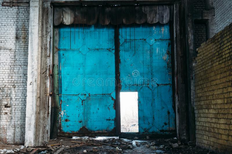 Grungy steel door in abandoned warehouse. Garage or factory storage gate stock photos