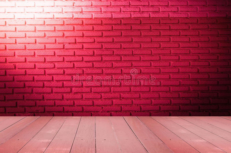 Grungy textured red brick and stone wall with warm brown wooden floor inside old neglected and deserted interior, masonry and carp. Entry brickwork concept stock image