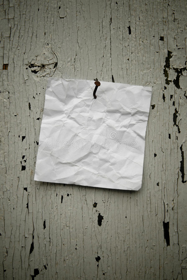 Grungy torn note paper nailed on rustic old weathered background stock images