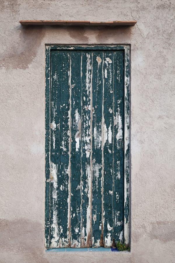 Grungy zielony drewniany drzwi w starej kamiennej ścianie zdjęcie royalty free