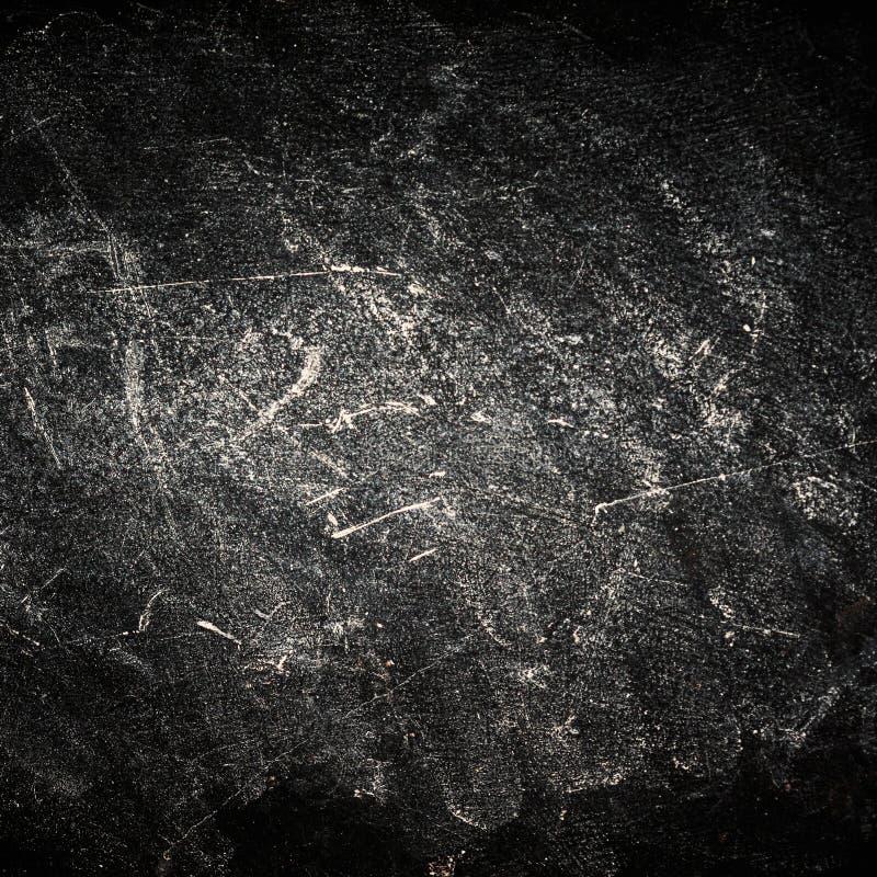 Grungy zwarte Achtergrond met schijnwerper en krassen Krijt rubb stock foto