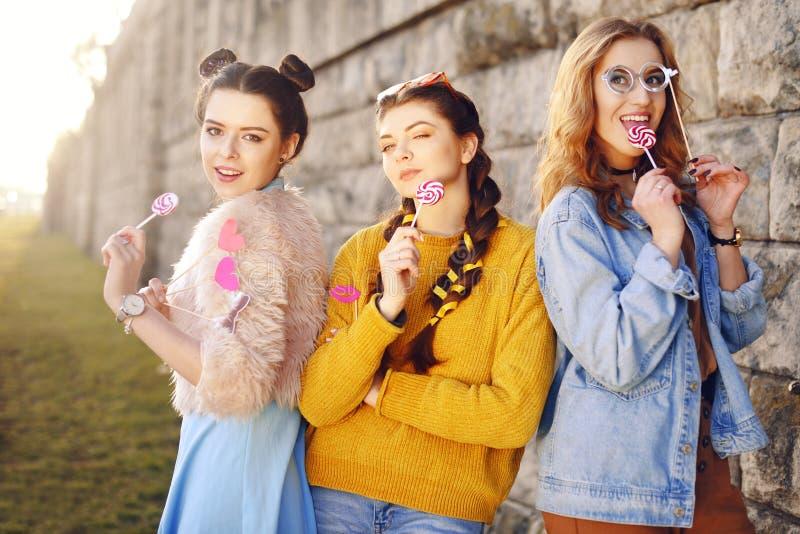 Grup de trois filles avec les lèvres drôles, verres, étoiles, coeurs de papier sur le bâton au coucher du soleil ayant l'amusemen photo stock