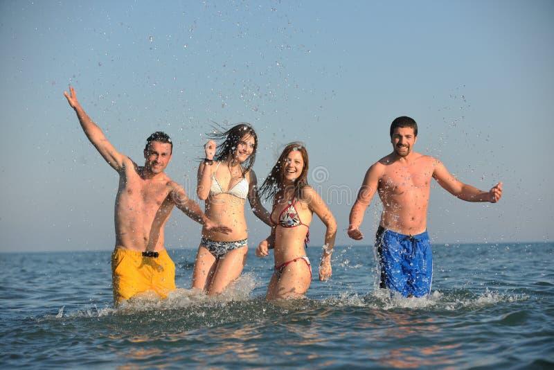 Grup szczęśliwi ludzie zabawę i bieg na plaży obrazy stock