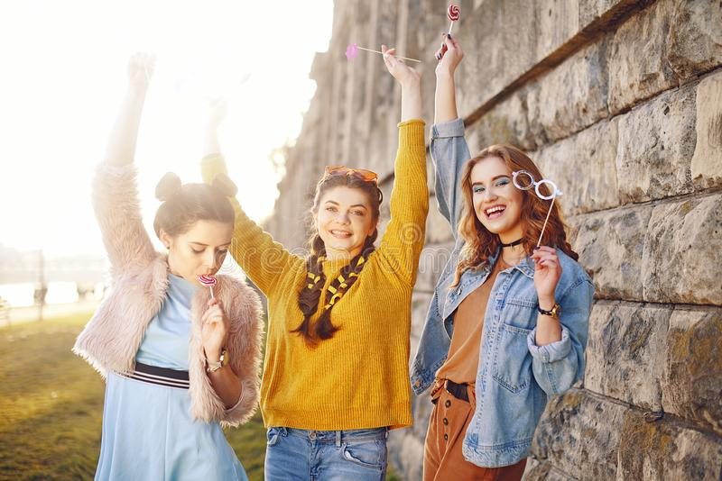 Grup of three girls with funny lips, glasses, stars, paper hearts on stick at the sunset having fun. Going crazy, smile at summer royalty free stock photo