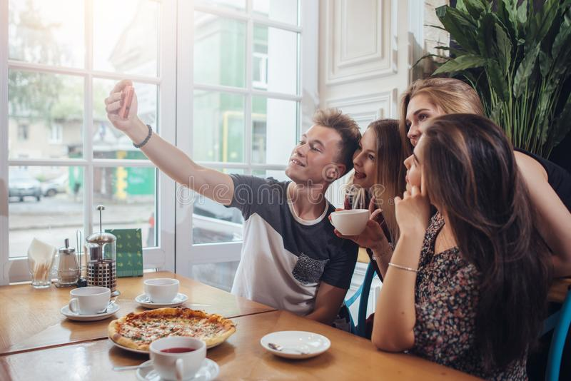 Grupa śliczni nastolatkowie bierze selfie z telefonem komórkowym podczas gdy siedzący w restauraci z wnętrzem w retro stylu obrazy stock