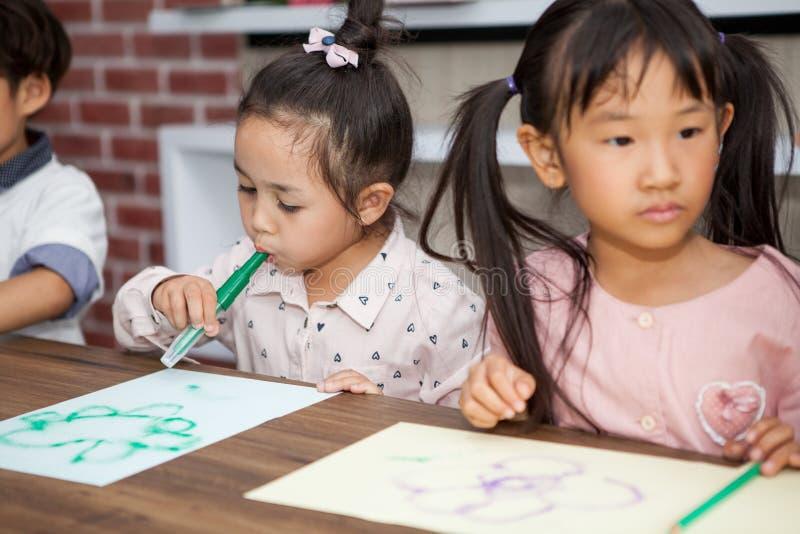 grupa Śliczny małej dziewczynki i chłopiec dmuchania koloru pióra studencki obraz wraz z pepiniera nauczycielem w sali lekcyjnej  zdjęcia royalty free