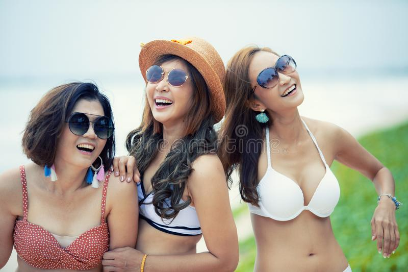 Grupa śmia się z szczęście emocją rozochocona azjatykcia młoda kobieta jest ubranym plażowego bikini zdjęcie stock