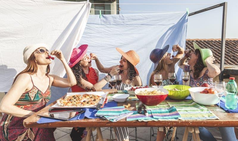 Grupa żeńscy przyjaciele ma zabawę podczas gdy jedzący wiśnie na dachach fotografia royalty free