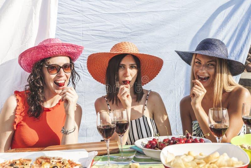 Grupa żeńscy przyjaciele ma zabawę podczas gdy jedzący wiśnie na dachach obraz royalty free