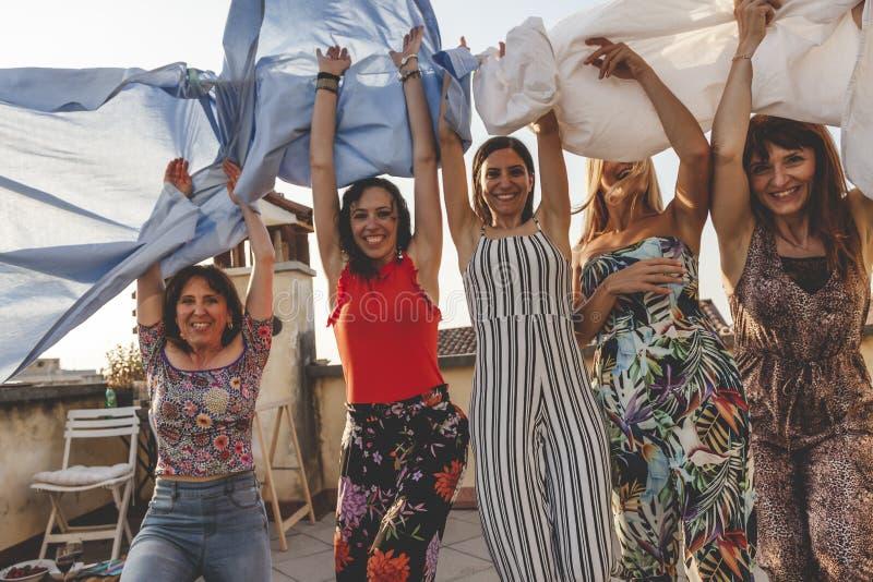 Grupa żeńscy przyjaciele na wakacje zabawę wśród prześcieradeł zdjęcia royalty free