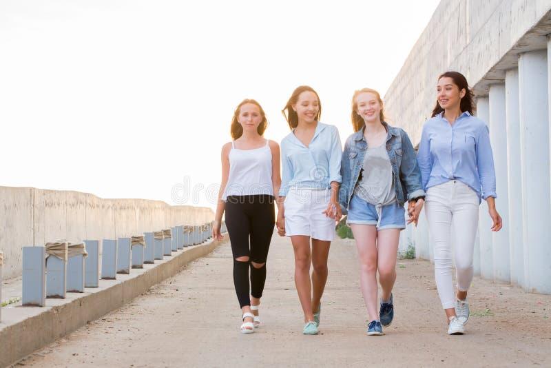 Grupa żeński przyjaciół chodzić plenerowy, opowiadający, mieć zabawę i uśmiech togethernes, przyjaźń, stylu życia pojęcie obraz royalty free