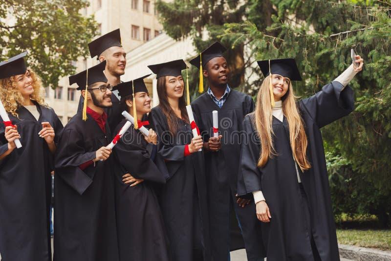 Grupa absolwenci świętuje selfie i robi obraz stock