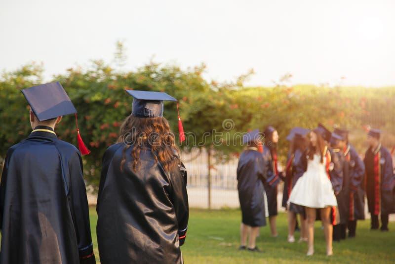 Grupa absolwenci podczas pocz?tku Poj?cie edukacji gratulacje w uniwersytecie Skalowanie ceremonia zdjęcia stock