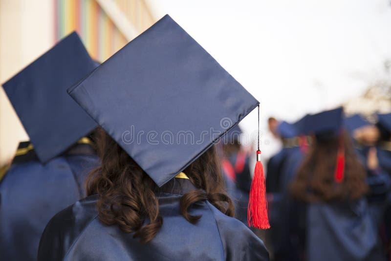 Grupa absolwenci podczas pocz?tku Poj?cie edukacji gratulacje w uniwersytecie Skalowanie ceremonia zdjęcie royalty free