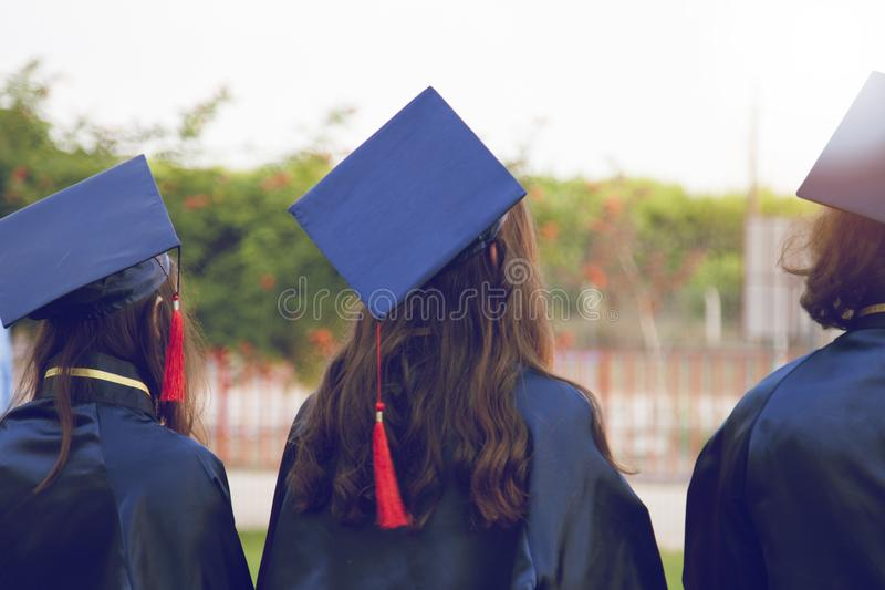 Grupa absolwenci podczas pocz?tku Poj?cie edukacji gratulacje w uniwersytecie Skalowanie ceremonia zdjęcia royalty free