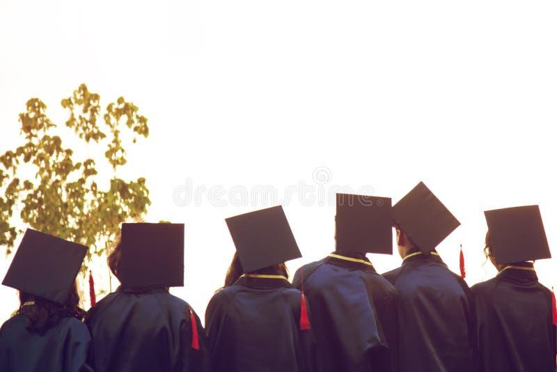 Grupa absolwenci podczas pocz?tku Poj?cie edukacji gratulacje w uniwersytecie Skalowanie ceremonia obrazy royalty free