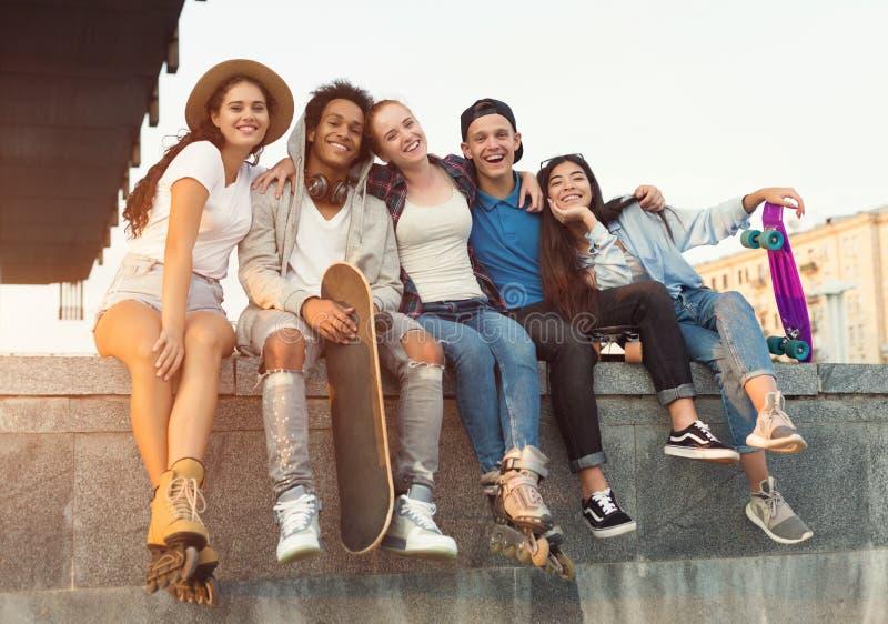 Grupa aktywni nastolatkowie śmia się wpólnie, miasto wieczór obraz stock