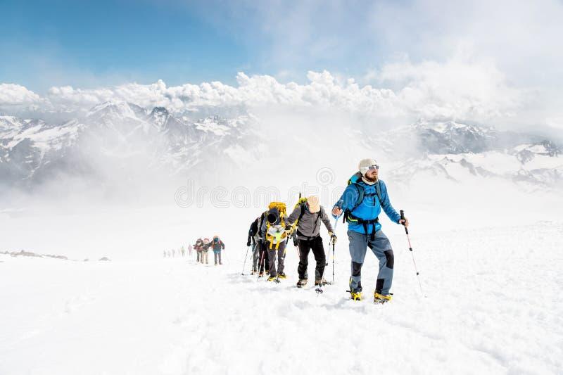 Grupa alpiniści wspina się wierzchołek nakrywająca góra obraz stock