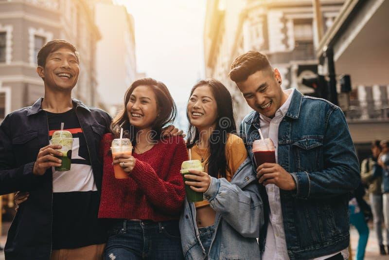 Grupa azjatykci przyjaciele z sokiem w mieście obrazy stock