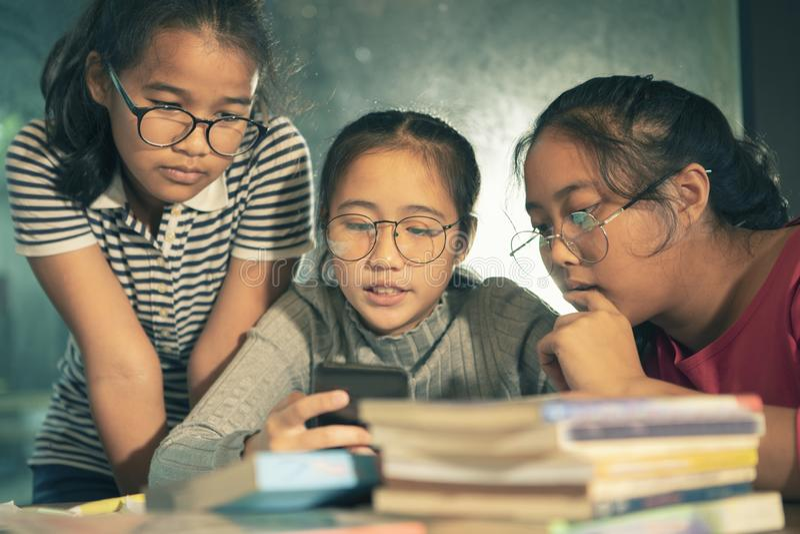 Grupa azjatykciego nastolatka czytelnicza wiadomość na mądrze telefonie obrazy stock