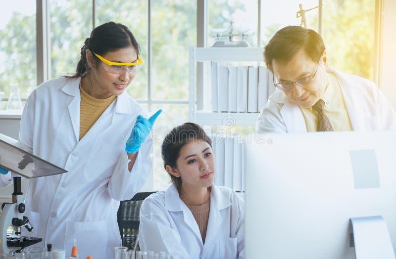 Grupa azjatykciego studenta medycynego badania nowy projekt z starszym profesorem wpólnie przy laboratorium obraz royalty free
