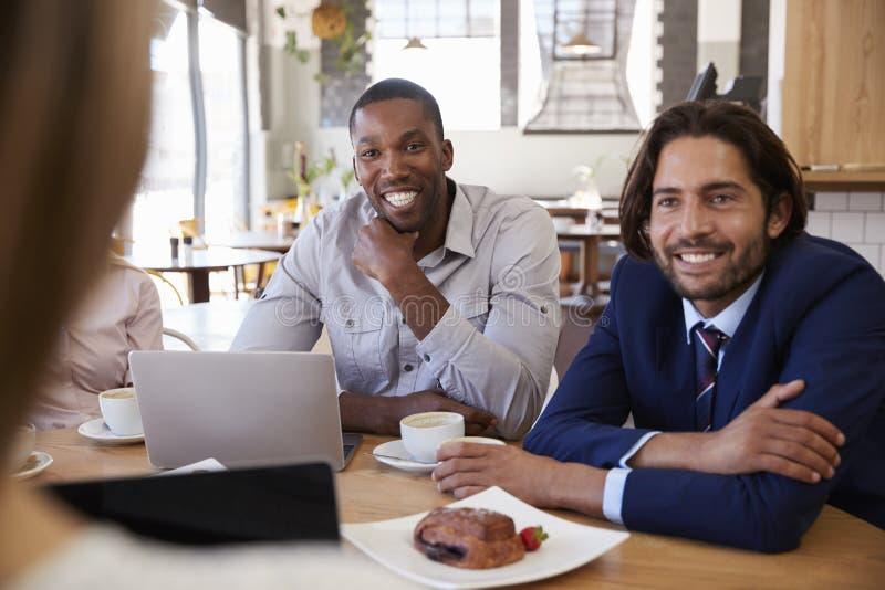 Grupa biznesmeni Ma spotkania W sklep z kawą obraz royalty free