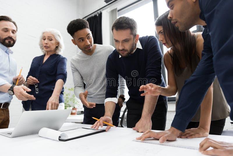 Grupa biznesmeni pracuje przy stołem w biurze obraz stock