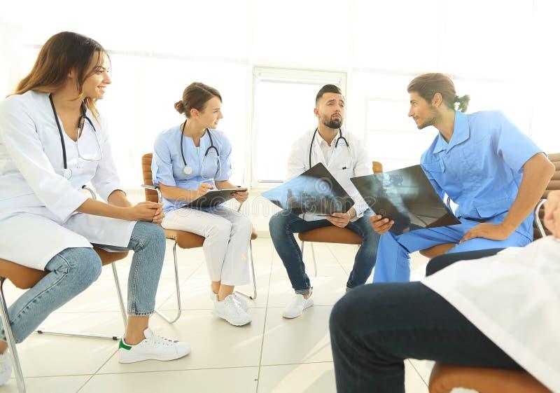 Grupa chirurdzy i medyczny fachowy personel dyskutuje na cierpliwym prześwietleniu obrazy stock