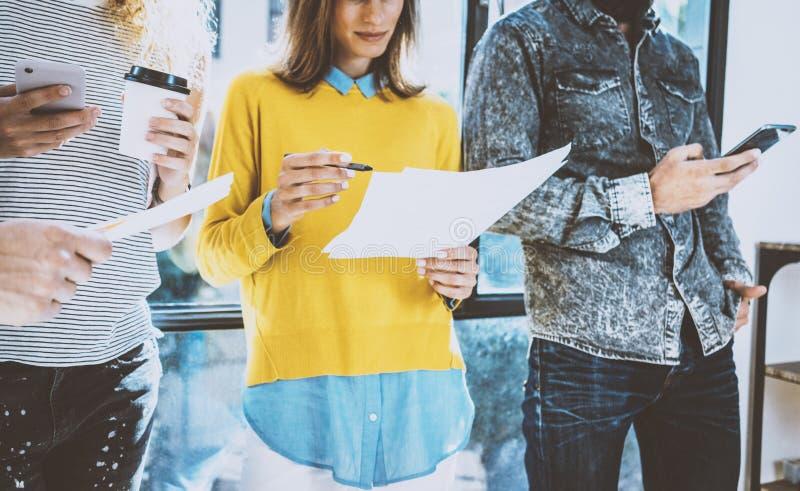 Grupa coworkers przyjaciele stoi przód i dyskutuje biznesowego pomysł okno w biurze Młoda kobieta trzyma a fotografia stock