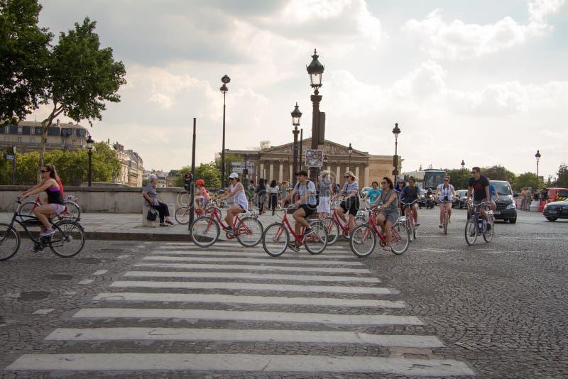 Grupa cykliści i samochody krzyżuje Pont De Los angeles Concorde i zgromadzenie narodowe w Paryż widok obrazy stock