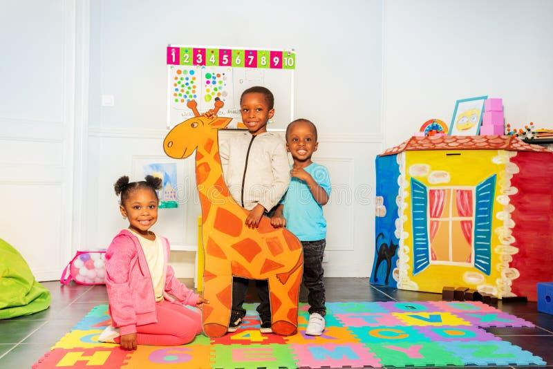 Grupa czarne chłopiec i dziewczyna trzymamy patroszonej żyrafy obraz royalty free
