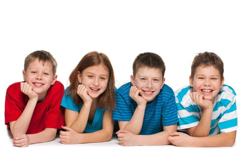 Cztery dziecka kłamają na podłoga fotografia stock