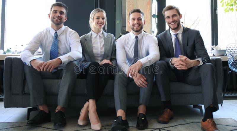 Grupa cztery ludzie biznesu siedzi na kanapie Jesteśmy drużyną ty potrzebujesz jeżeli ty chcesz udawać się zdjęcie stock