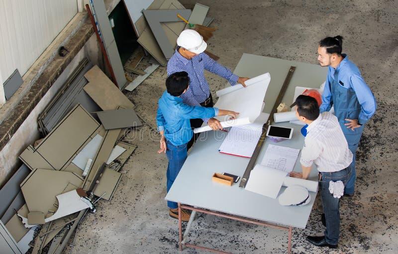 Grupa cztery ludzie wliczając inżyniera i biznesmeni dyskutujemy i przegląd o materiale budowlanym, brać od ptasich oczu widoku zdjęcie stock