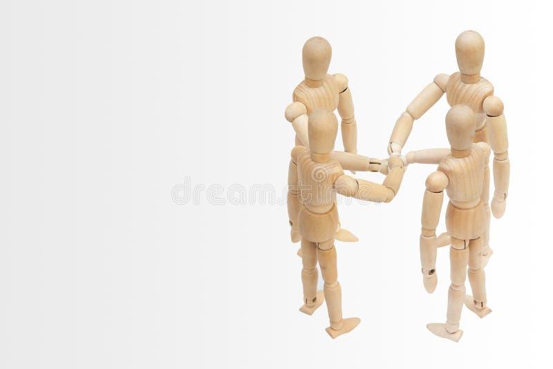 Grupa drewniana postaci mannequin kładzenia sterta ich ręki wpólnie obrazy stock