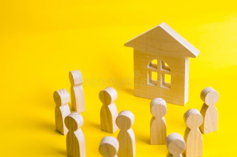 Grupa drewniane postacie ludzie otacza drewnianego dom i patrzeje Młodzi ludzie w poszukiwaniu niedrogiego budynek mieszkalny Poż zdjęcia stock