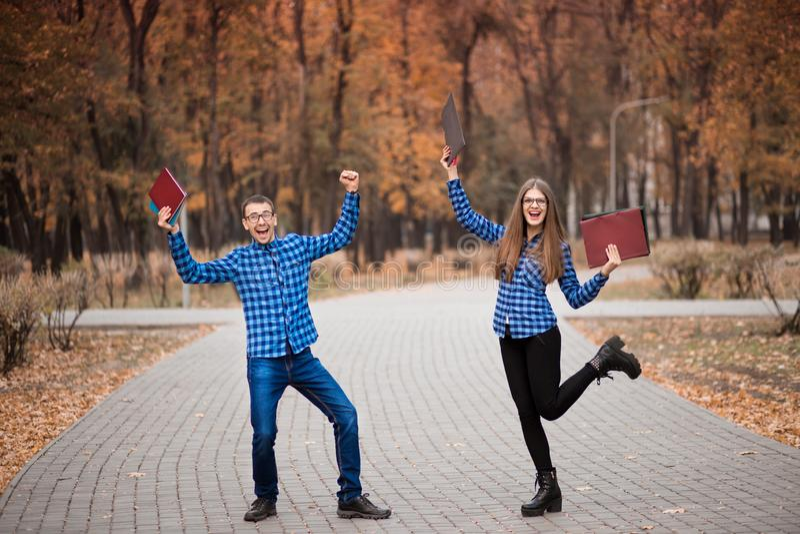 Grupa dwa młodych euforycznych uczni szczęśliwy przechodzący egzamin z rękami w górę spaceru w parku obrazy royalty free