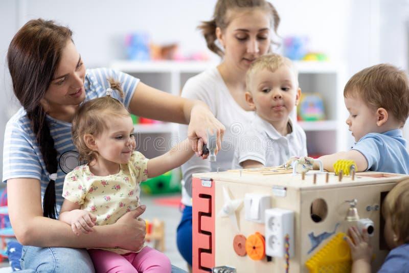 Grupa dzieci bawiąca się w ośrodku opieki dziennej lub przedszkolu obraz royalty free