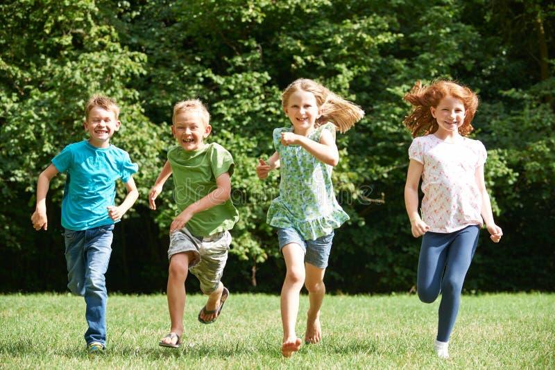Grupa dzieci Biega W kierunku kamery W boisku zdjęcie stock