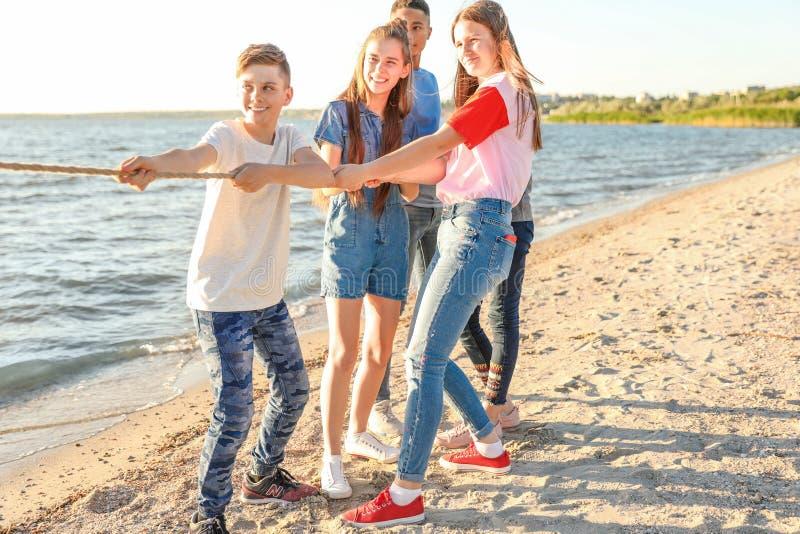 Grupa dzieci ciągnie arkanę podczas zażartej rywalizaci gry na plaży Obóz letni zdjęcia royalty free
