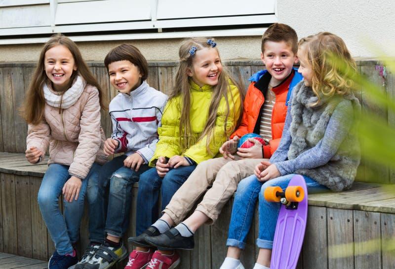 Grupa dzieci siedzi na ławce obraz stock