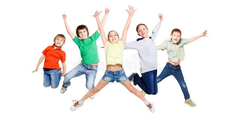 Grupa dzieci skacze przy białym odosobnionym pracownianym tłem zdjęcie royalty free