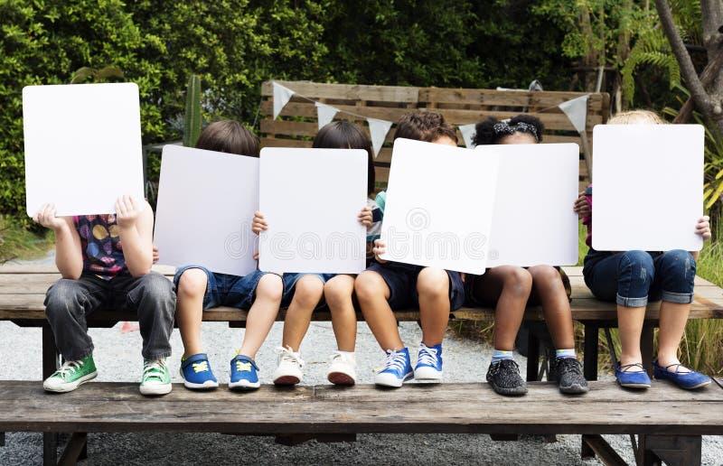Grupa dzieci trzyma pustą sztandar pokrywę ich twarz zdjęcie royalty free