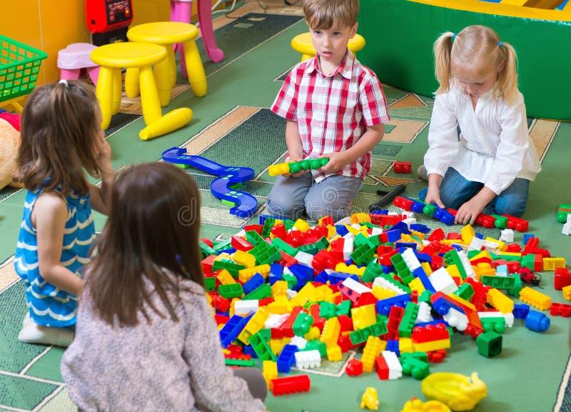 Grupa dzieciaki bawić się z kolorowym konstruktorem zdjęcie royalty free