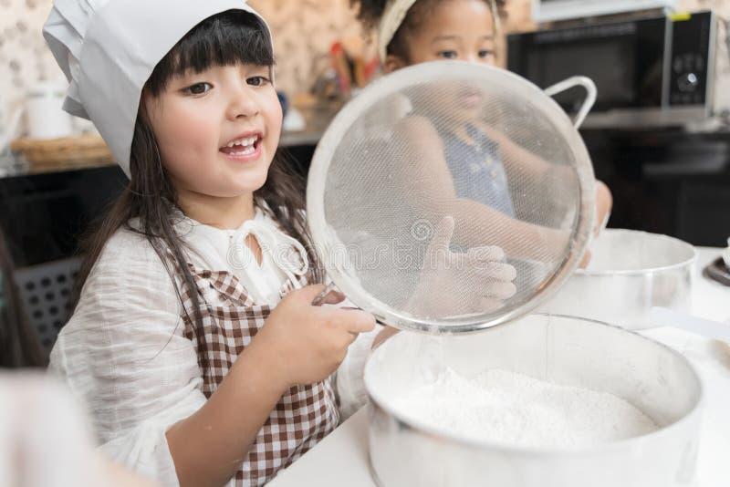 Grupa dzieciaki przygotowywa piekarnię w kuchni Dzieci uczy się kulinarni ciastka fotografia stock