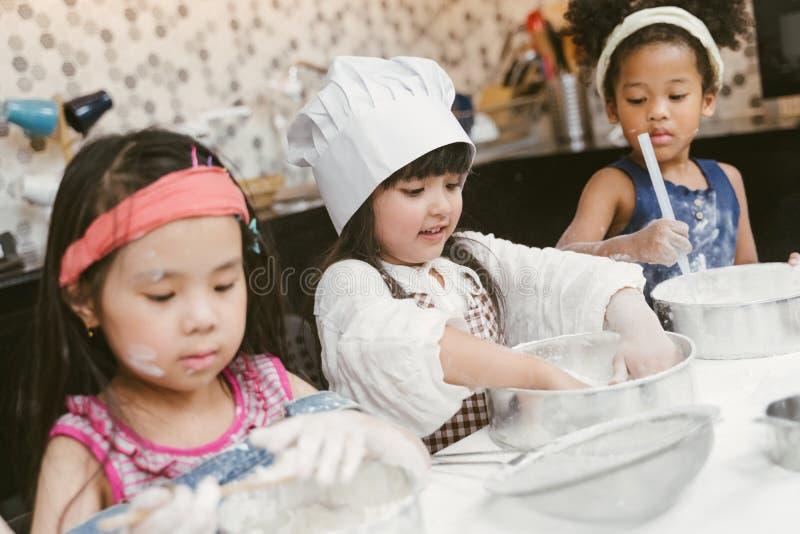 Grupa dzieciaki przygotowywa piekarnię w kuchni Dzieci uczy się kulinarni ciastka obrazy royalty free